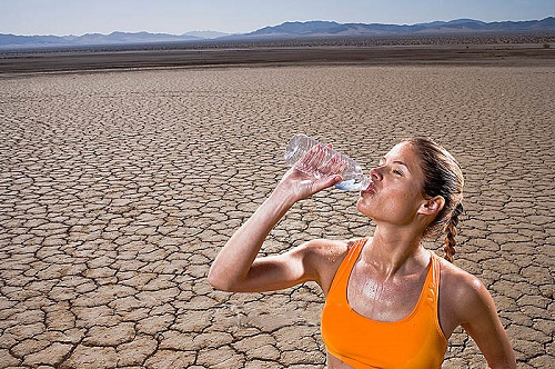 Runner Drinking Bottled Water in Desert